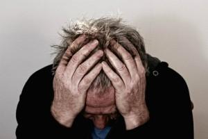 Billedet viser en nedbrudt mand. Siden handler om traumatisk stress på arbejdet.