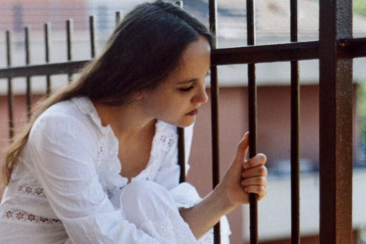 Billedet viser en indespærret kvinde. Siden handler om vold i parforholdet og PTSD.