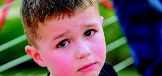 Billedet viser en sørgmodig dreng. Siden handler om psykiskamishandling i barndommen.