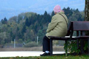 Billedet viser en ældre kvinde der sidder alene på en bænk. Siden handler om PTSD hos ældre.