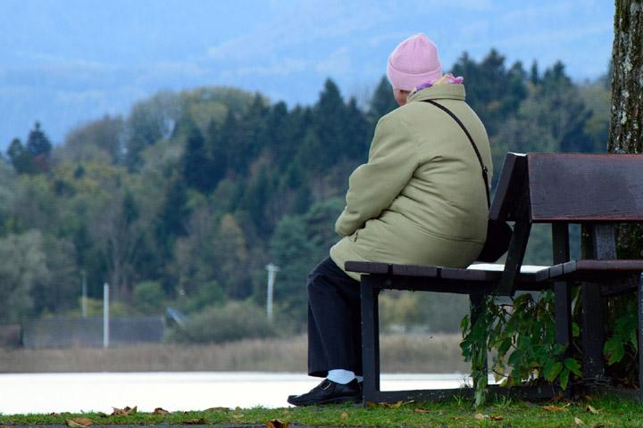 Billedet viser en ældre kvinde sidder alene på en bænk. Siden handler om PTSD hos ældre.
