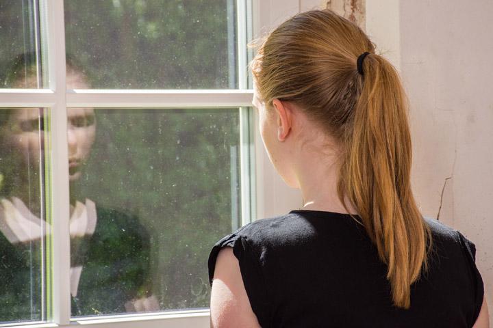 Billedet viser en kvinde der kigger på sit eget spejlbillet. Siden handler om en kvinde, der ikke er den hun har været.