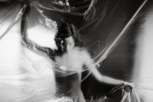 Fotoet viser en kvinde gemt bag sløret plast. Fotoet er af Vilizar Ivanov. Siden handler om depersonalisering og derealiserings forstyrrelse.