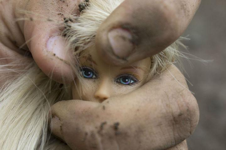 Billedet viser en hånd, der masser en barbiedukke. Siden handler om forskellen på PTSD og Kompleks PTSD.