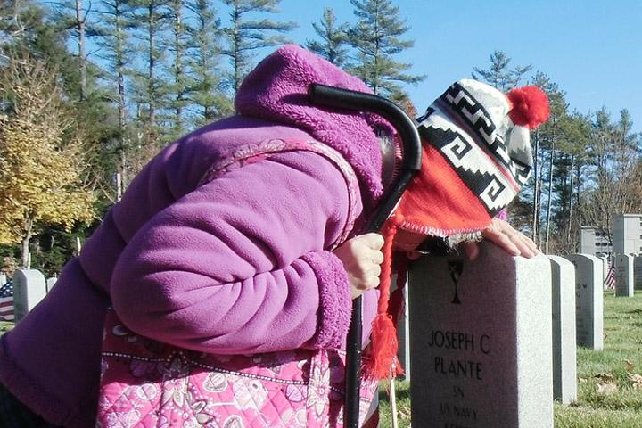 Billedet viser en sørgende kvinde foran en gravsten. Siden handler om hvordan man mindsker retraumatiseret.