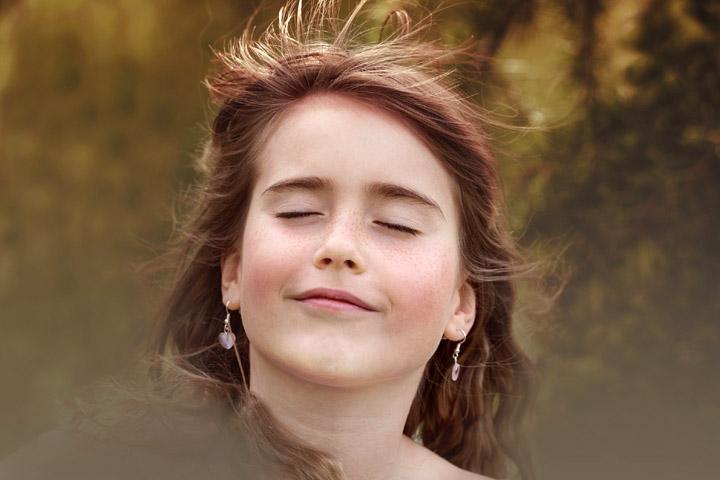 Billedet viser en kvinde der lnyder vinden og solen. Siden handler om mindfulness.