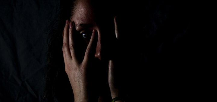 Fotoet viser en kvinde i mørke. Siden handler om en grundlæggende følelse af ikke at være god nok. Fotoet er taget af Melanie Wasser.